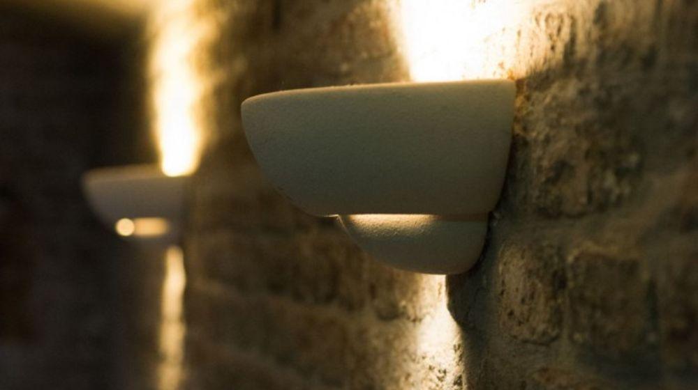 Detailaufnahme einer indirekten Beleuchtung an der Backsteinmauer im Innenbereich