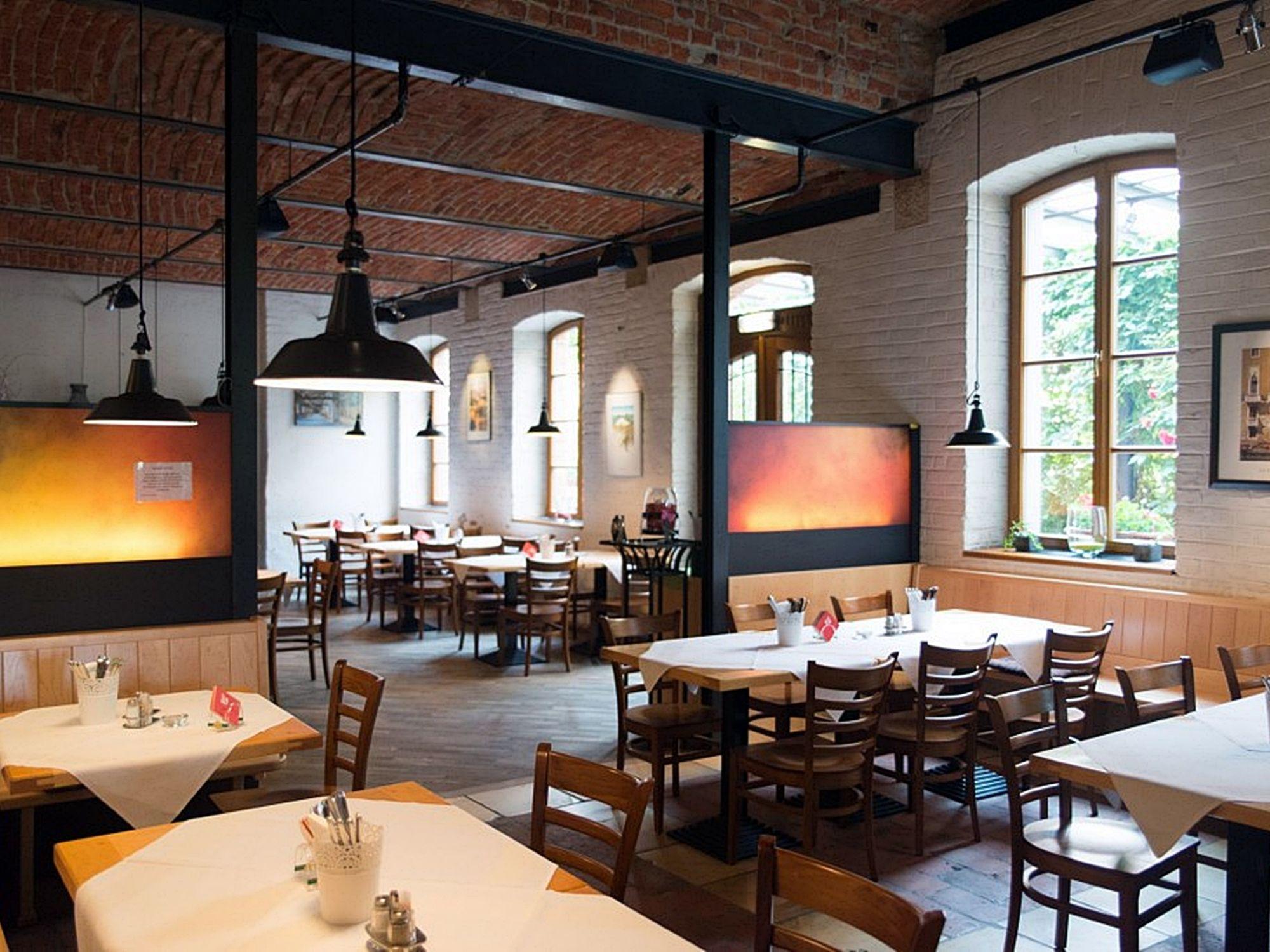 Innenraum der Gaststätte mit Sitzplätzen und stimmungsvoller Beleuchtung