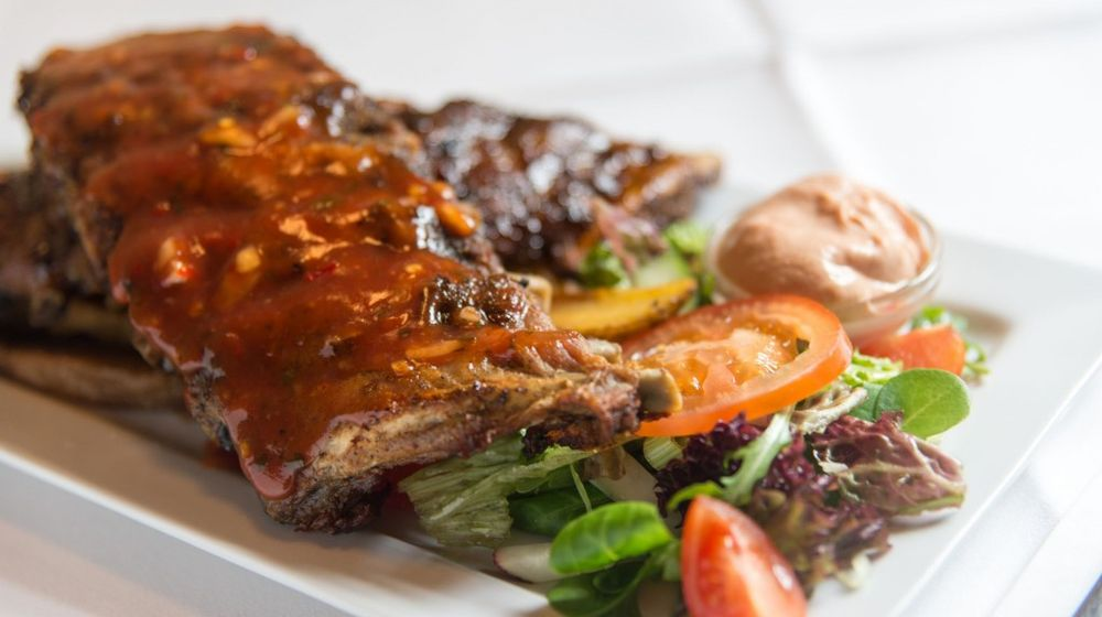Close-up of a food plate with pork ribs on salad, next to cutlery