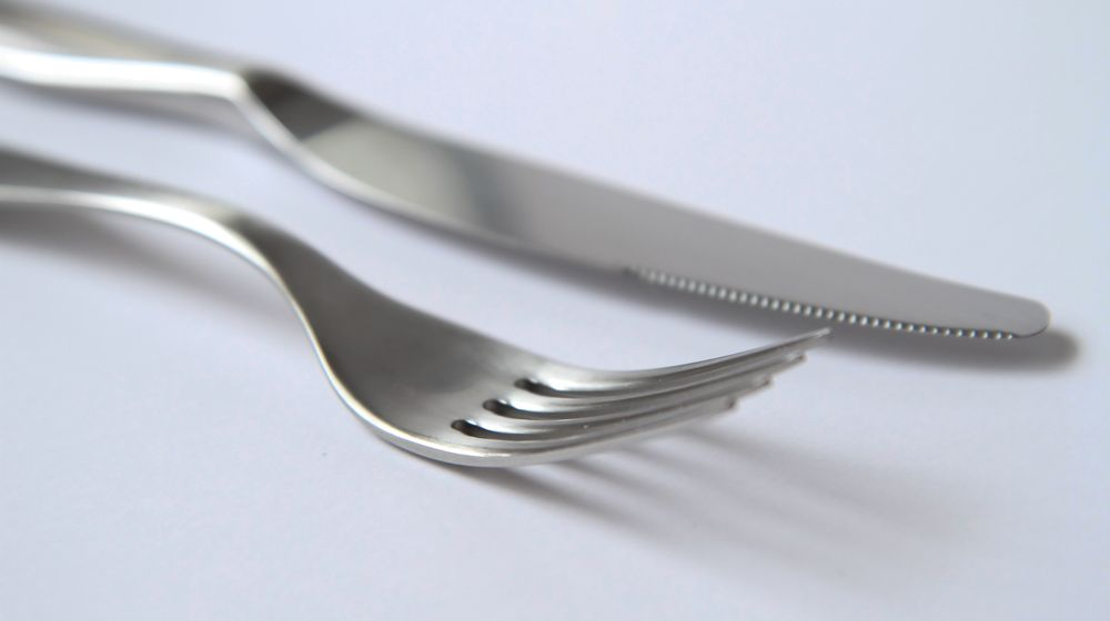 Detail view of fork and knife on white tablecloth