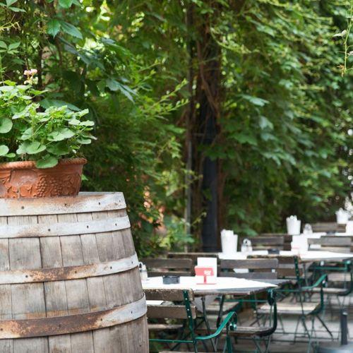 Blick vom blumengeschmückten Weinfass auf die gedeckten Tische im Gastgarten